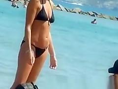 Topless women puts sun cream on face