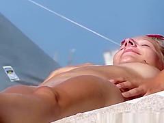 Guy rubs nudist clit at beach