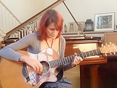 Redhead playing guitar down blouse and cleavage