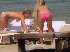 Topless girls relaxing by the beach