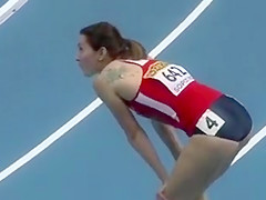Athletic woman runs around the track in a flimsy outfit