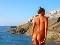 Tight tanned teen plays nude in the ocean
