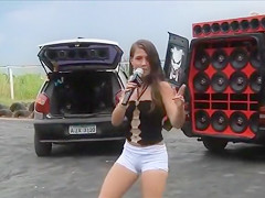 Teen Latina dancing and singing in a parking lot