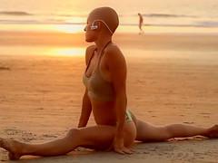 Bald beauty doing yoga by the sea