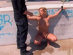 Tied up busty Spanish blonde on the beach